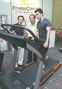 Fit for all: Au Yong (left) explaining characteristics of a Fitness Concept treadmill to Olympic Council of Malaysia secretary Datuk Sieh Kok Chi as Fitness Concept ambassador Kevin Zahri demonstrates on the treadmill.